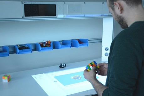 A solution in a few easy steps: A smart workbench shows how to solve a Rubik's cube.