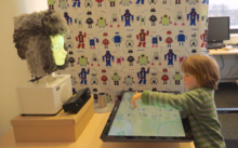 Together with a robot head, a child practices guessing animals as part of a study for the BabyRobot project. The robot is meant to learn from their interaction how to best indicate which animal the child should look for. Photo: BabyRobot