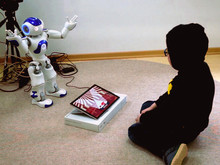 In the L2TOR project, the robot supports children in their learning by gesturing. The animal that the child should learn the word for in a foreign language is displayed on the tablet. Photo: L2TOR