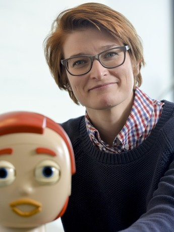 In her dissertation project, Jasmin Bernotat – here with the robot head Flobi – studies the effects of stereotypes on humans and robots. Photo: CITEC/Bielefeld University
