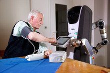 Robots in nursing care: With the assistance of the robot caregiver Care-O-bot (Fraunhofer IPA) the user transfers the measurement results. Photo: Fraunhofer IPA