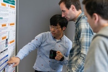 Doctoral researcher Taeho Kim, from the Cluster of Excellence CITEC, presents his poster to RIO organizer Dr. David Wright (Manchester Metropolitan University) and others.