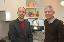 Dr. Thomas Hermann (left) und PD Dr. Sven Wachsmuth (right) are heading the project together with Prof. Dr. Britta Wrede. The avatar Flobi (center) provides support in the kitchen to the apartment's guests. Photo: CITEC/Bielefeld University