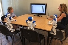 Three robots together with child and researcher